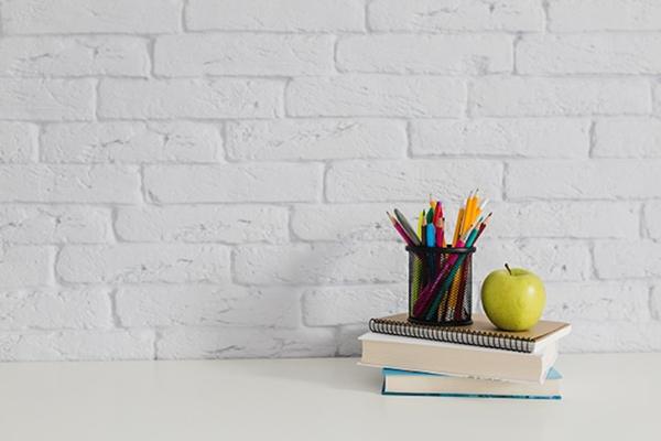 Pennor och ett äpple står på ett par böcker med en vit tegelvägg i bakgrunden.